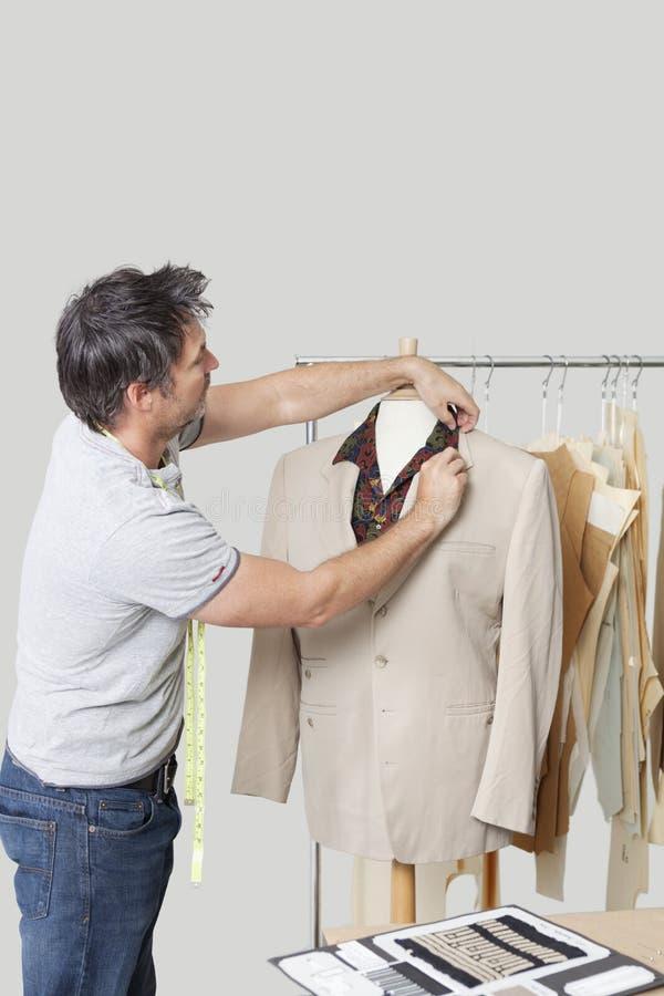 Männliche Damenschneiderin, die Anzug auf der Attrappe des Schneiders im Entwurfsstudio justiert stockfotos