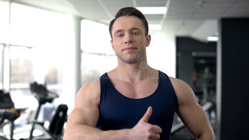 Männliche darstellende Daumen des Athleten oben, Training in der Turnhalle, Sportergebnisse, gesunder Lebensstil lizenzfreies stockbild