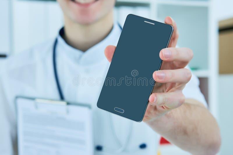 Männliche Doktor ` s Hand, die einen leeren intelligenten Telefonschirm zeigt lizenzfreies stockbild