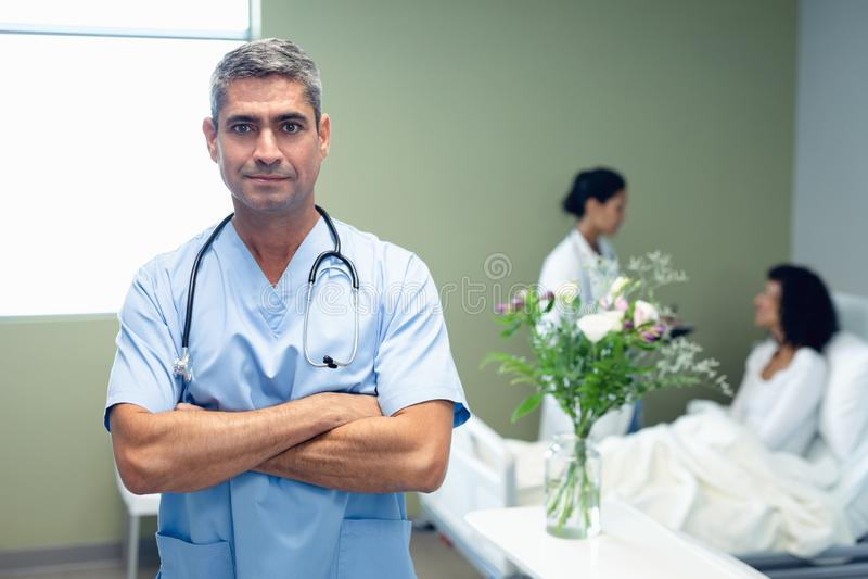 Männliche Doktorstellung mit den Armen gekreuzt im Bezirk am Krankenhaus lizenzfreie stockfotografie