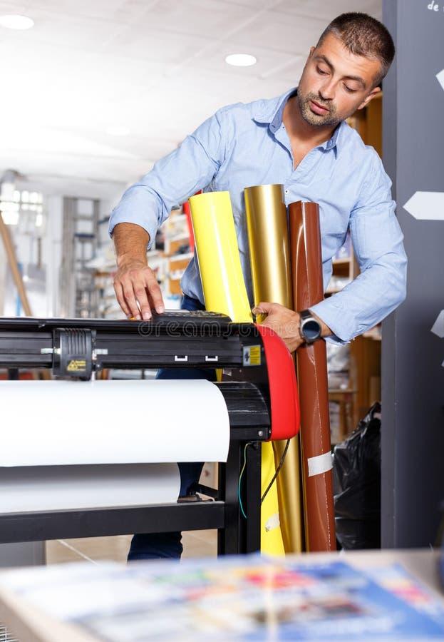 Männliche Druckarbeitskraft mit Rollen des farbigen Papiers stockbilder