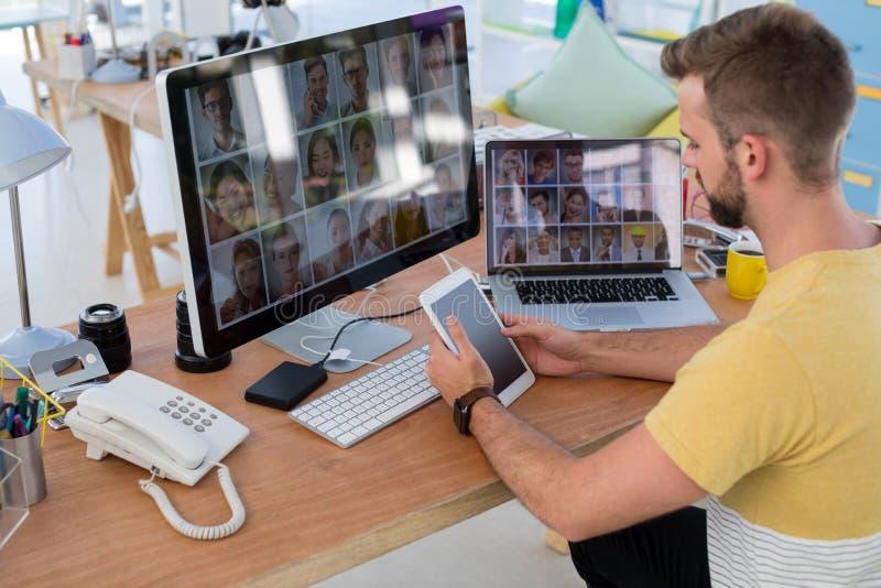 Männliche Exekutive, die digitale Tablette am Schreibtisch verwendet stockbild