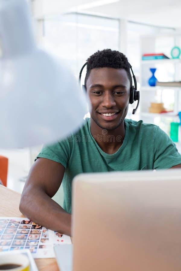 Männliche Exekutive im Kopfhörer, der über Computer an seinem Schreibtisch arbeitet stockbild