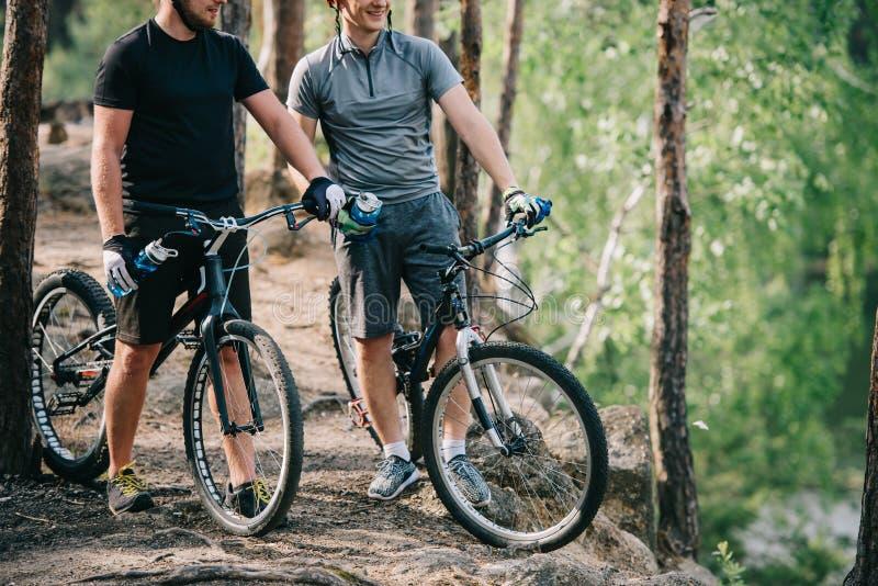 männliche extreme Radfahrer in den Sturzhelmen mit den Mountainbiken, die bei den Sportflaschen Wasser liegen lizenzfreie stockfotos