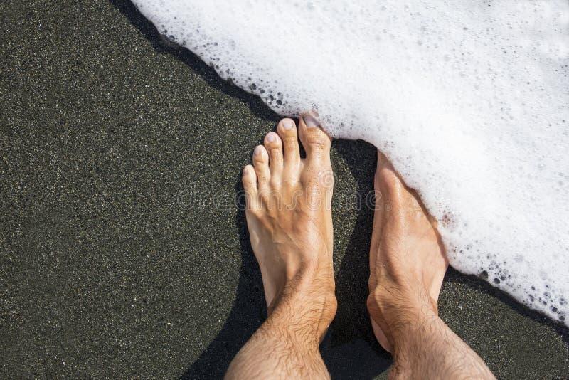 Männliche Füße auf dem schwarzen vulkanischen Sand bedeckt mit weißer Gischt minimalismus geometrisch diagonal lizenzfreies stockfoto