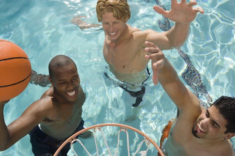 Männliche Freunde, die Basketball im Pool spielen stockbild