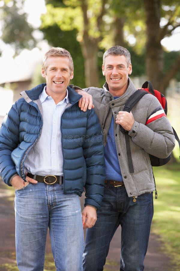 Männliche Freunde, die in Herbst-Park gehen lizenzfreie stockbilder