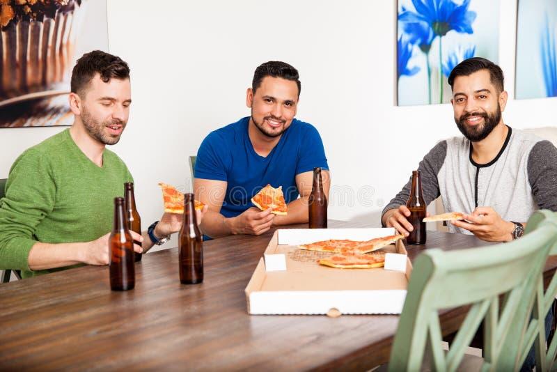 Männliche Freunde, die zu Hause Pizza essen stockbilder