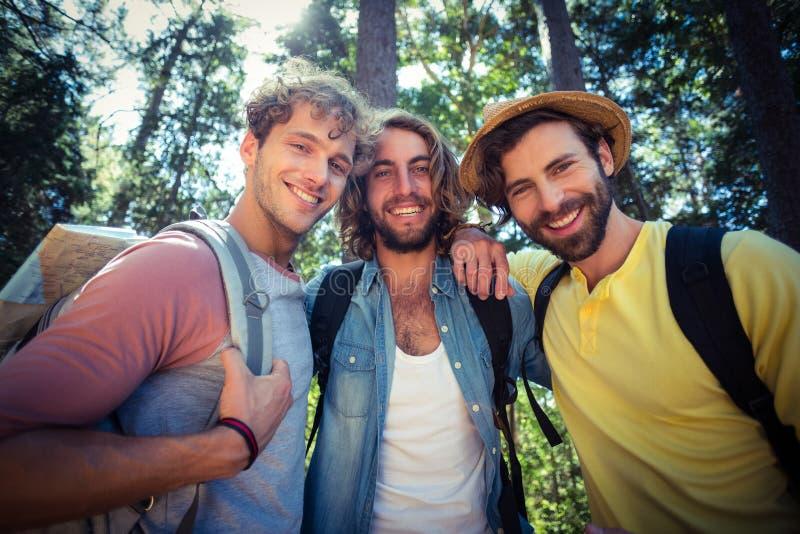 Männliche Freunde, die zusammen im Wald stehen lizenzfreies stockfoto