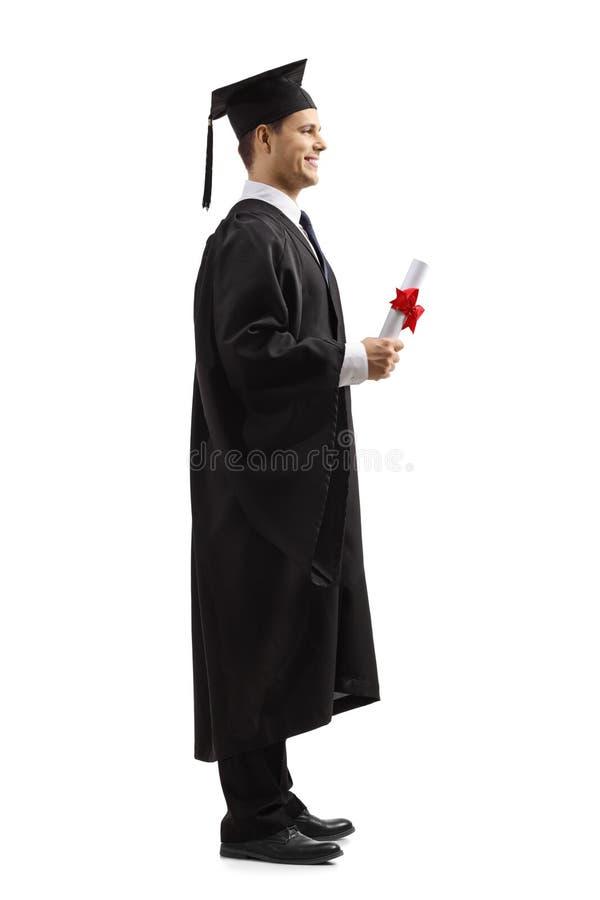 Männliche graduierte Stellung und Halten eines Diploms stockfotos