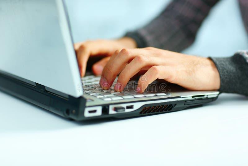 Männliche Hände, die auf Laptoptastatur schreiben stockfotos
