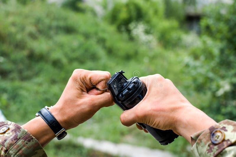 Männliche Hände, die eine Handgranate für airsoft halten stockfotografie