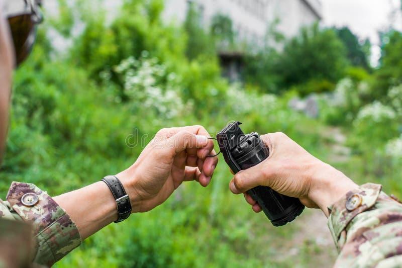 Männliche Hände, die eine Handgranate für airsoft halten stockfotos