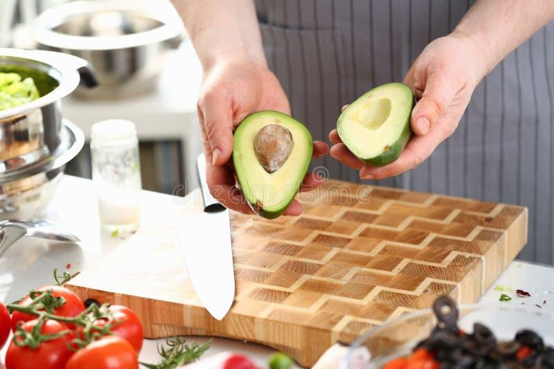 Männliche Hände, die grüne Avocatofrucht-Hälften halten stockfotos
