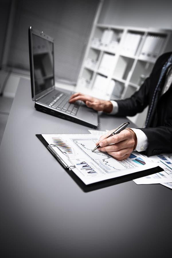 Männliche Hände, die Schreibarbeit mit Stift und Laptop tun lizenzfreie stockfotos