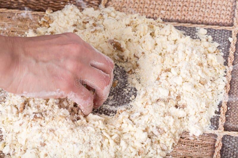 Männliche Hände, die Teig mit Walnüssen machen lizenzfreies stockbild
