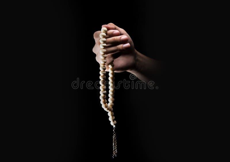 Männliche Hände, die unter Verwendung der Gebetsperlen über dunklem backgroud beten lizenzfreie stockfotos