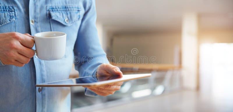 Männliche Hände, die weiße digitale Tablette und Tasse Kaffee halten lizenzfreies stockfoto