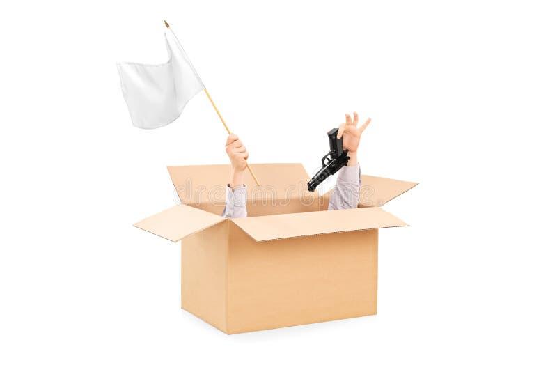 Männliche Hände, die weiße Flagge und Gewehr innerhalb eines Kastens halten lizenzfreies stockfoto