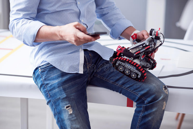 Männliche Hände, die wenig Roboter und Handy halten lizenzfreie stockfotos
