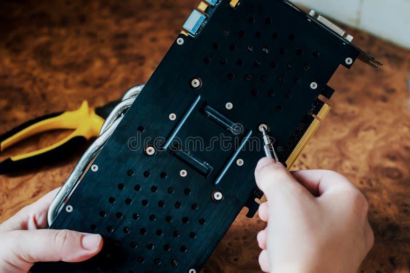 Männliche Hände halten einen Schraubenzieher und eine Reparaturcomputer-animations-Karte stockbild