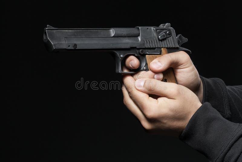 Männliche Hände mit dem Gewehr lokalisiert auf Schwarzem stockfotografie