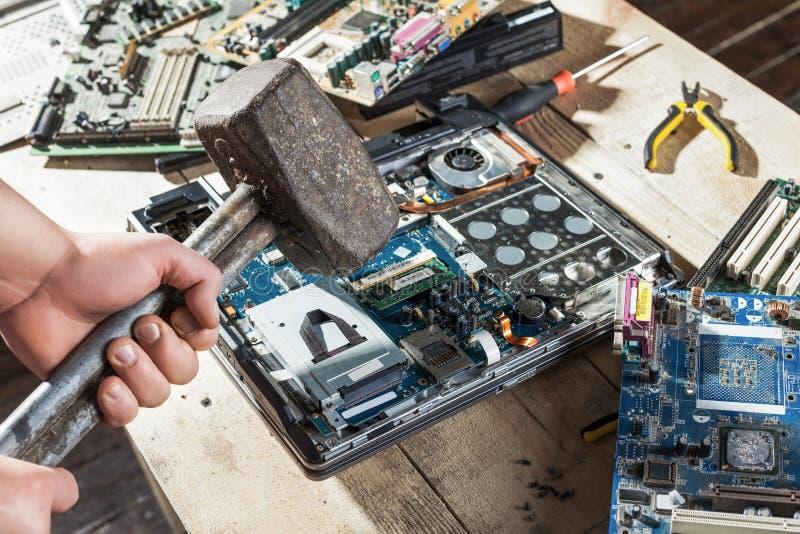 Männliche Hände mit Vorschlaghammer bremst Laptopnahaufnahme lizenzfreie stockbilder