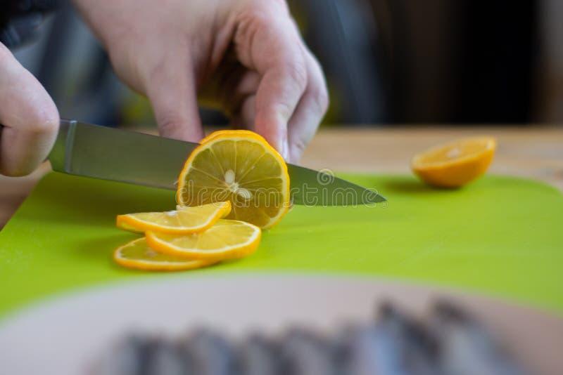 Männliche Hände schnitten Zitrone auf grünem Schneidebrett, Abschluss oben stockbilder