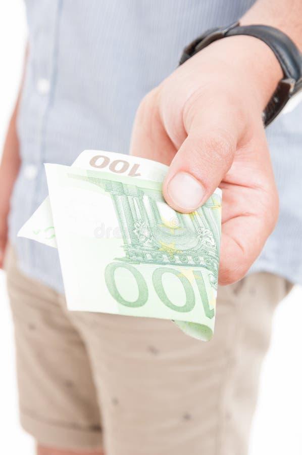 Männliche Hand in der Nahaufnahme bietet Geld an stockfoto