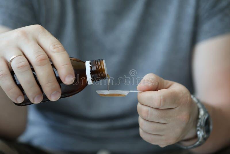 Männliche Hand des Mannes im Krankenhaus gießt Husten stockbild