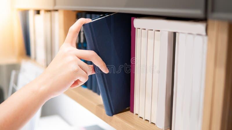 M?nnliche Hand, die blaues Buch auf B?cherregal ausw?hlt stockbild