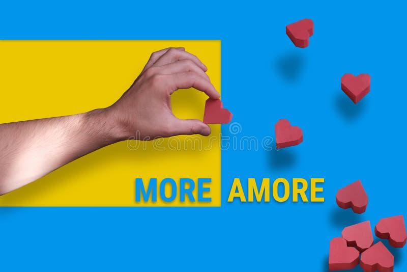 Männliche Hand, die ein Herz auf einem gelb-blauen Hintergrund hält Viele Herzen wie Gleiche fallen mit Text mehr amore ab lizenzfreies stockbild
