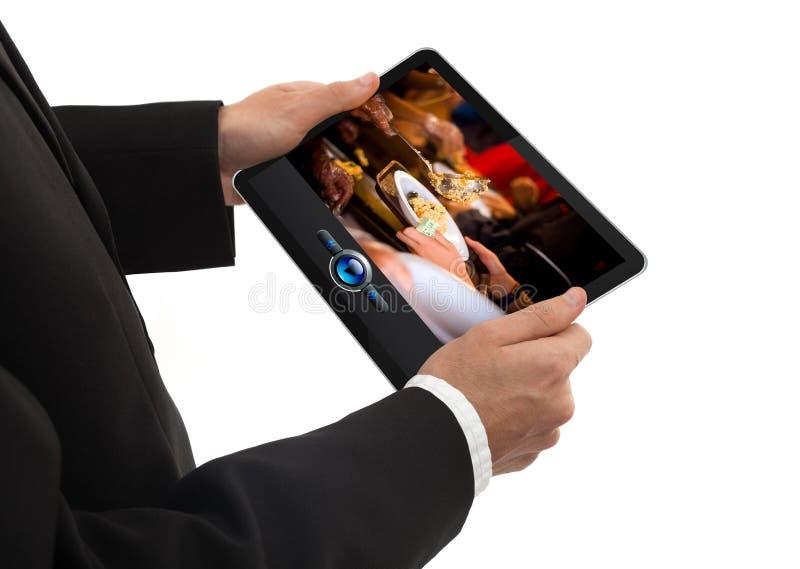Männliche Hand, die einen Berührungsflächen-PC zeigt einen Film anhält stockbild