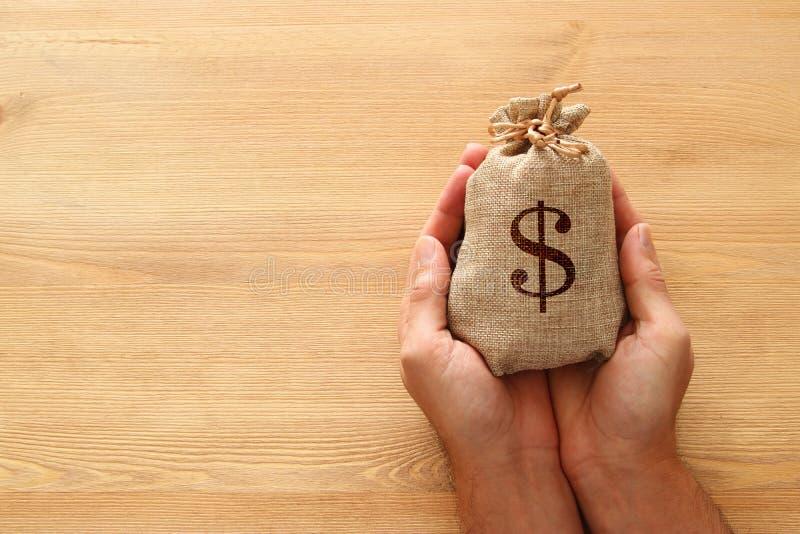 Männliche Hand, die einen Sack Geld über hölzernem Schreibtisch hält lizenzfreie stockbilder