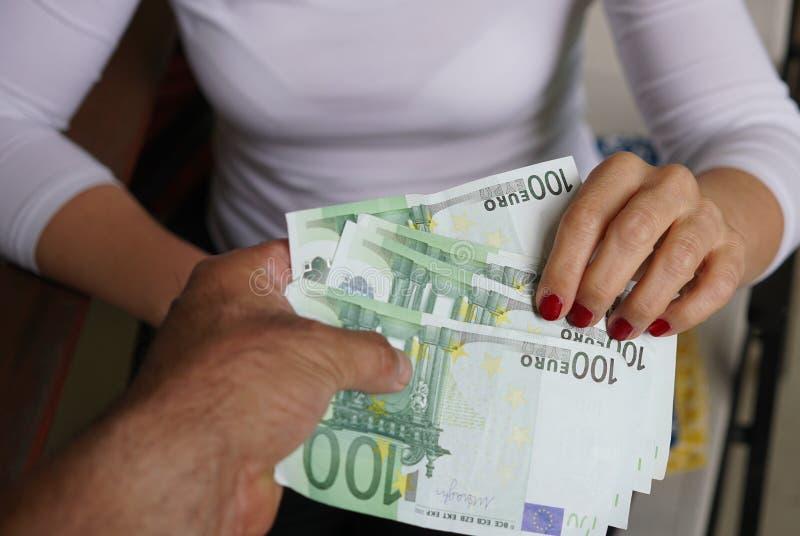 Männliche Hand, die einer Frau Geld gibt lizenzfreie stockfotografie