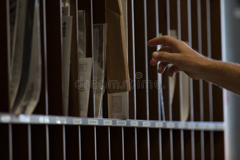 Männliche Hand, die für sortierten Posten oder Post erreicht stockfotografie