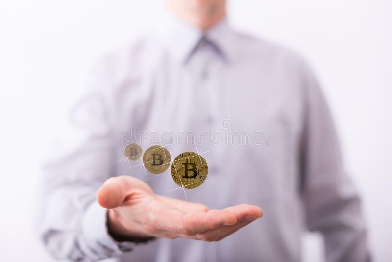 Männliche Hand, die frei schwebende Münzen von bitcoin darstellt lizenzfreie stockfotos