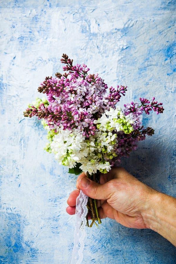 Männliche Hand, die lila Blumenblumenstrauß hält stockfoto