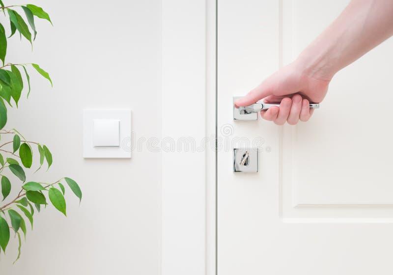 Männliche Hand, die modernen Türgriff hält Nahaufnahmeelemente des Innenraums der apartmen stockfoto