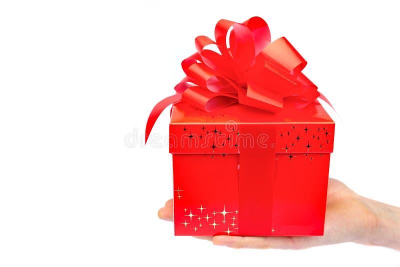 Männliche Hand, die roten Weihnachtskasten auf flacher Hand darstellt stockbild