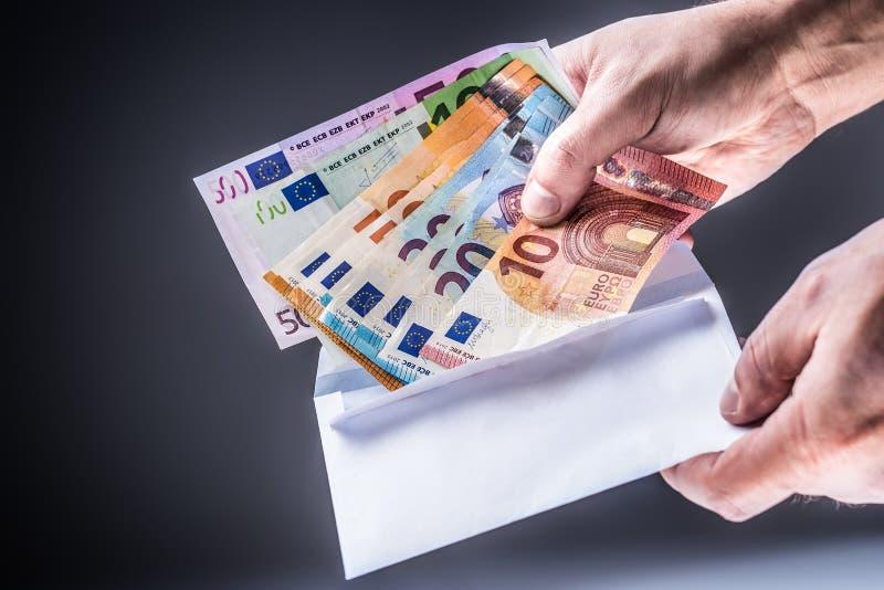 Männliche Hand eingefügt in die Umschlageurobanknoten - Bestechungsgeld und Korruptionskonzept stockbilder
