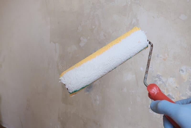 M?nnliche Hand im blauen Handschuh, der eine Farbenrolle h?lt Nicht-vergipster Betonmauerhintergrund Das Konzept der Hauptreparat lizenzfreies stockfoto