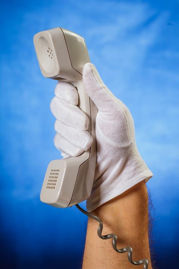 Männliche Hand im weißen Handschuh, der Überlandleitungstelefonempfänger hält lizenzfreie stockfotos
