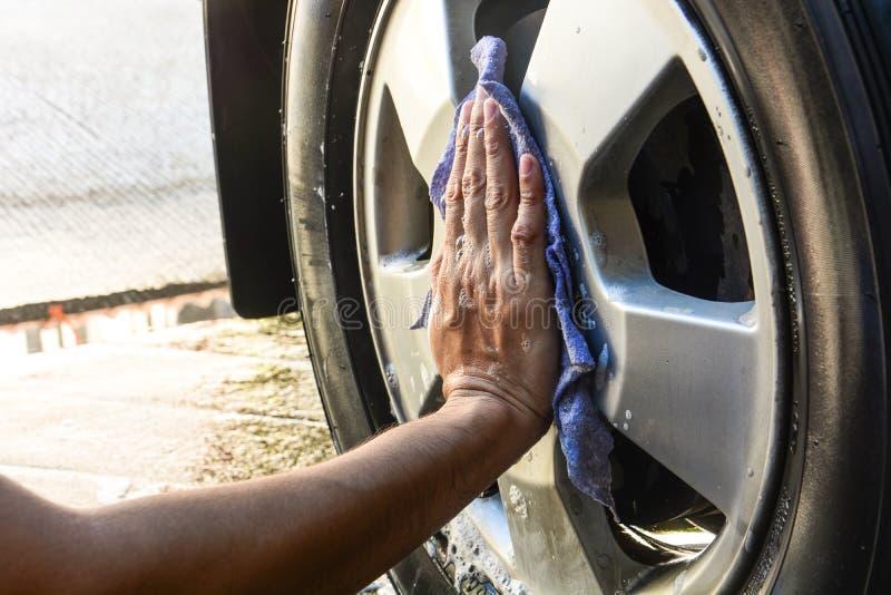 Männliche Hand mit blauem Stoffreinigungs-Radauto stockfoto