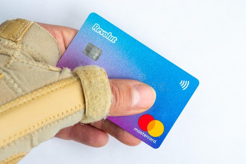 Männliche Hand mit einer Handgelenkklammer, die eine Revolut-Karte hält Revolut Ltd. bietet Lohn-pro-tägige Krankenversicherun lizenzfreie stockbilder