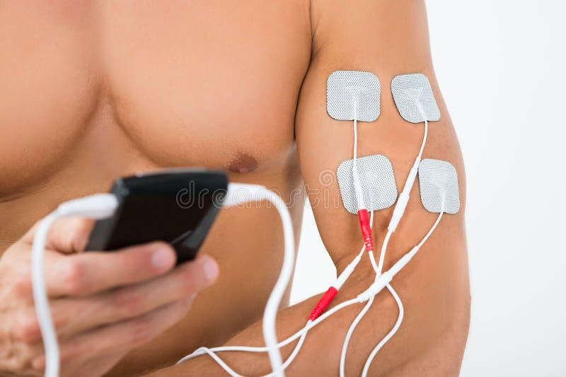 Männliche Hand mit electrostimulator Elektroden lizenzfreies stockfoto