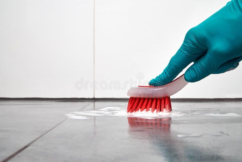 Männliche Hand mit roter Bürstenreinigung, die das Badezimmer auf dem Boden mit Ziegeln deckt lizenzfreie stockbilder
