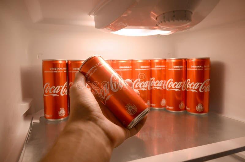 Männliche Hand stellt dar, dass rotes Getränk der Coca Cola innerhalb des inländischen Kühlvorrichtungskühlschranks voll von Koks stockbilder