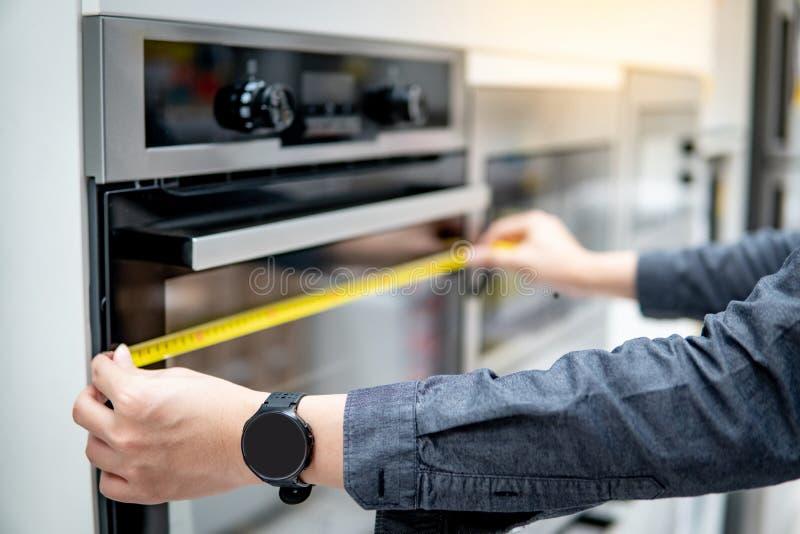 Männliche Hand unter Verwendung des Maßbandes auf Ofen lizenzfreie stockfotos