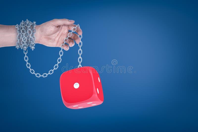 M?nnliche Hand verkettet an rote W?rfel auf blauem Hintergrund stockbilder